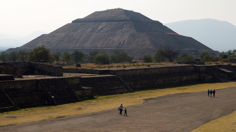 Pyramid of the Sun, Teōtīhuacān. Teōtīhuacān reached its peak from the 1st to the mid-6th century C.E. The main structures include the Pyramids of the Sun and the Moon, Avenue of the Dead, and the Temple of Quetzalcoatl (feathered serpent). Teotihuacan was home to as many as 125,000 people. The name Teōtīhuacān was given by the Aztecs long after the city had been abandoned c. 550 C.E. The original name is lost.