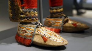 Anishinaabe outfit (detail), c. 1790, collected by Lieutenant Andrew Foster, Fort Michilimackinac (British), Michigan, Birchbark, cotton, linen, wool, feathers, silk, silver brooches, porcupine quills, horsehair, hide, sinew; the moccasins were likely made by the Huron–Wendat people (National Museum of the American Indian, Smithsonian Institution)