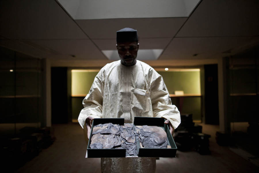 Deputy Director Abdoulaye Cisse shows a burnt manuscript at the Institut des Hautes Etudes et de Recherche Islamiques Ahmed Baba in Timbuktu, North of Mali. Thousands of manuscripts were destroyed by jihadists during the occupation, and many were hidden and saved at the Institute or by owners Timbuktu, December 05, 2013 (photo MINUSMA/Marco Dormino, CC BY-NC-SA 2.0)