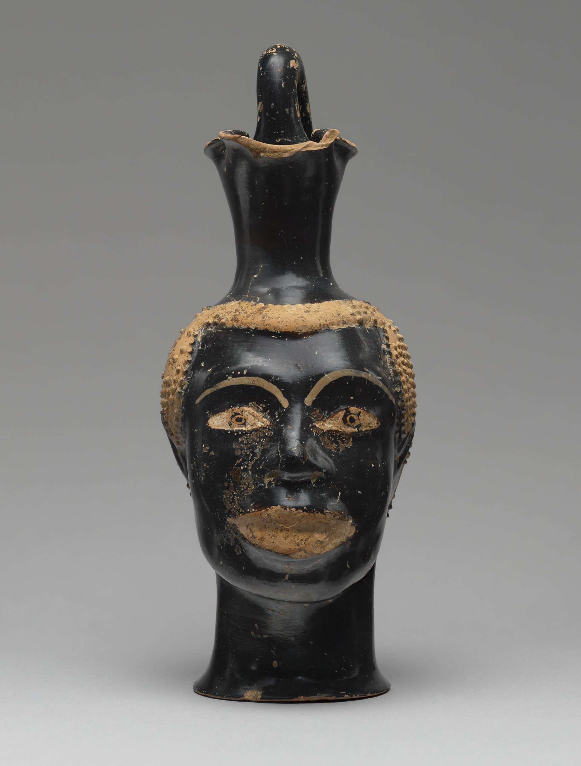 Pitcher (Oinochoe) in the Form of the Head of an African, about 510 B.C.E., attributed to Class B bis: Class of Louvre H 62. Terracotta, 8 7/16 inches high (The J. Paul Getty Museum, 83.AE.229. Digital image courtesy of the Getty's Open Content Program)