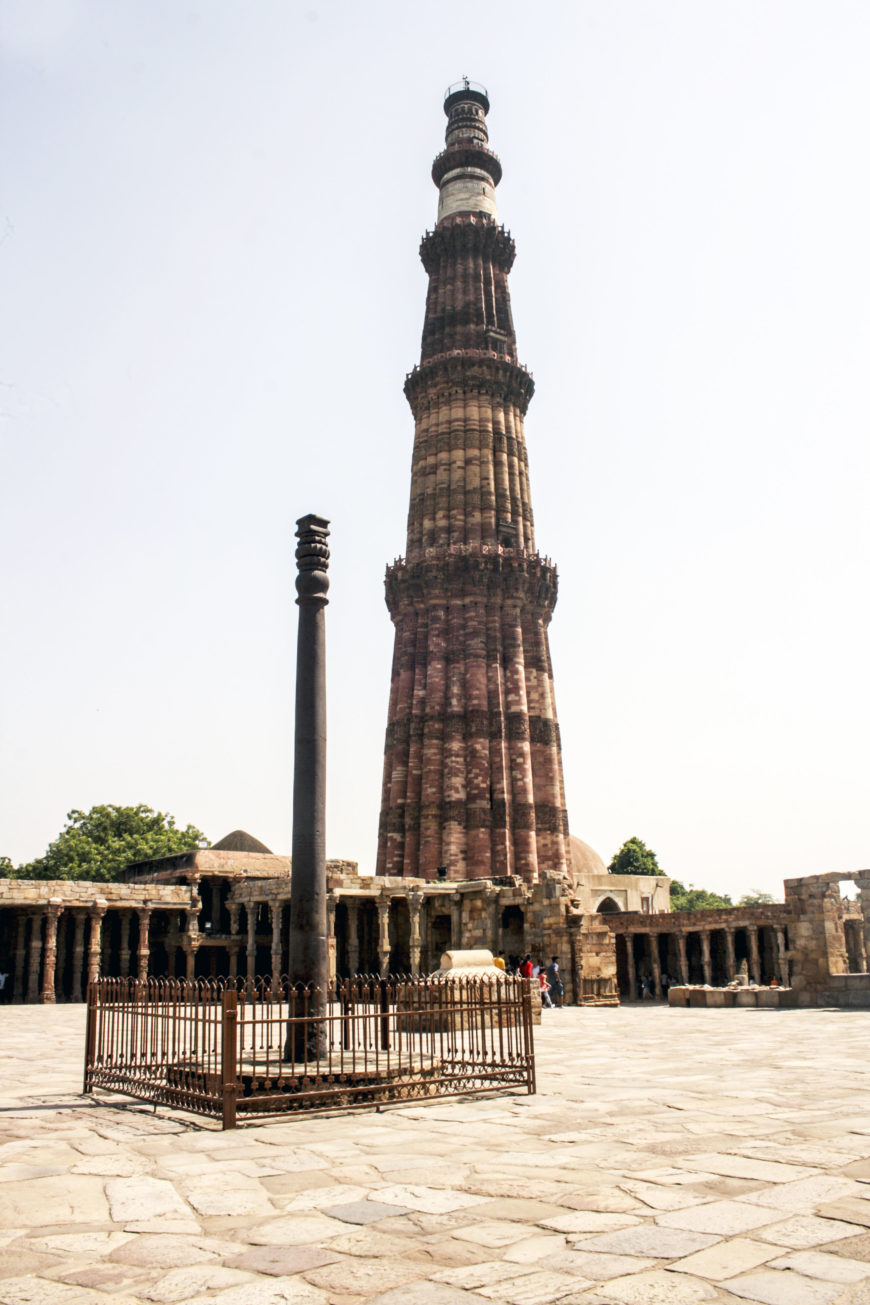 The 238 foot tall Qutb Minar in the background, c. 1192, Qutb archaeological complex, Delhi (photo: Indrajit Das, CC BY-SA 4.0). In the foreground is a c. 4th – 5th century iron pillar and the 12th century Qutb mosque.